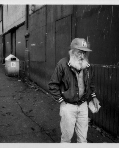 Elderly homeless man walking on sidewalk