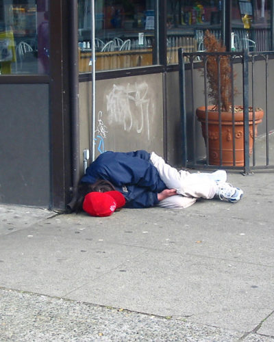 Photo of homeless man lying on sidewalk