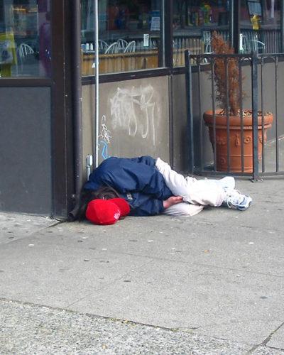 Photo of homeless man lying on sidewalk