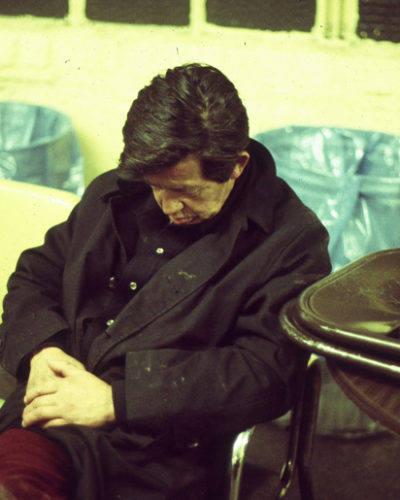 Photo of homeless man asleep on a chair