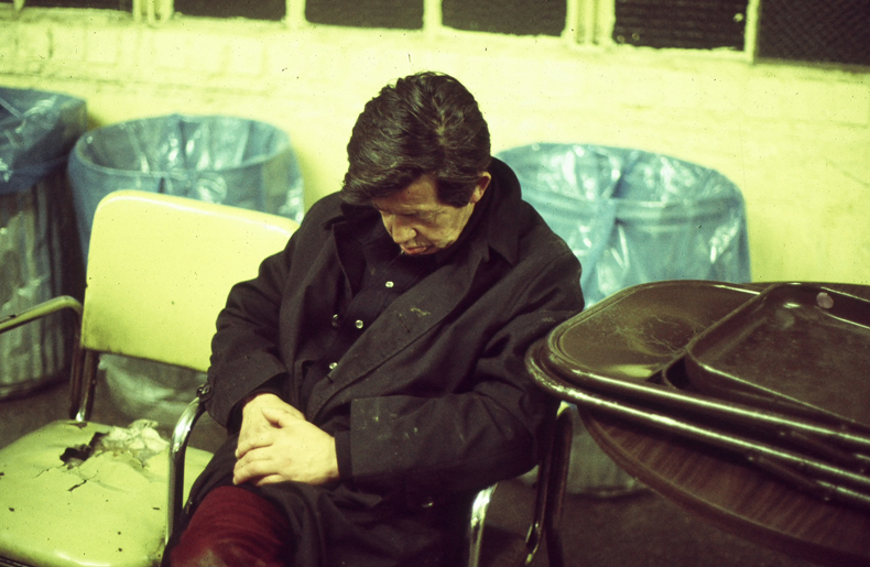 Photo of homeless man asleep on a chair